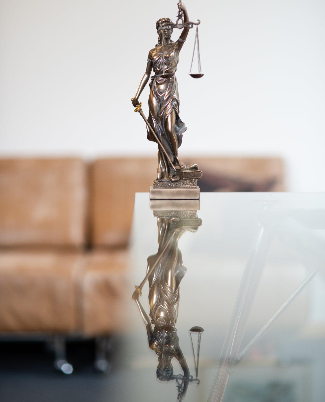 Justitia Statue bei Menge Noack Rechtsanwälte, die sich im Glastisch spiegelt
